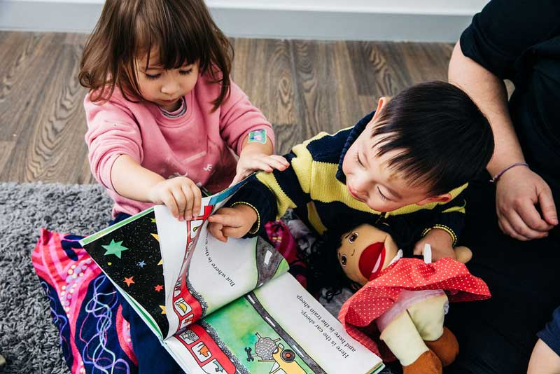 Children play with book mimicking pointing and developing reading skills