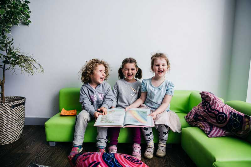 Three children laughing, share one book together. Sharing helps teach empathy to children.