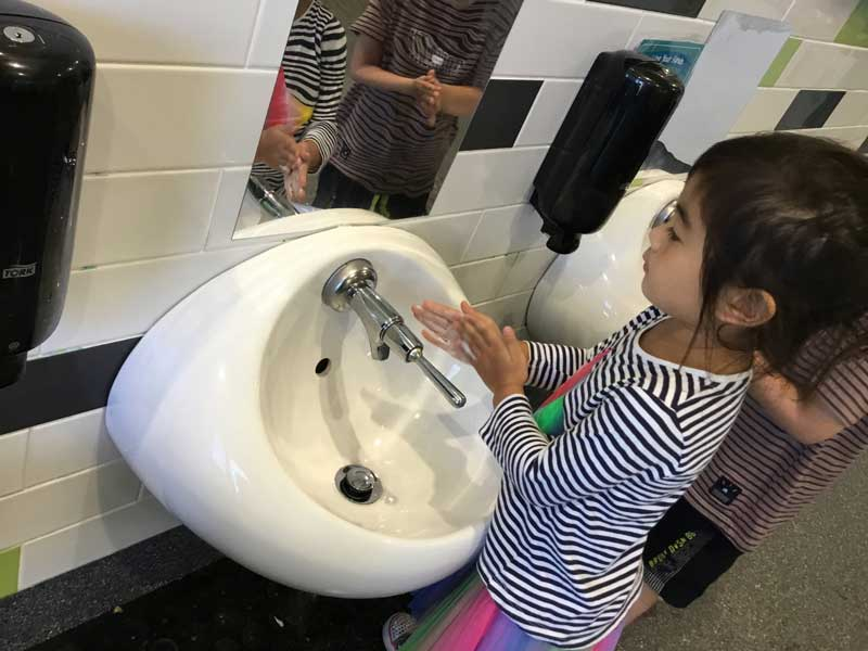 Children learn how to wash their hands to help stop the spread of infectious diseases.
