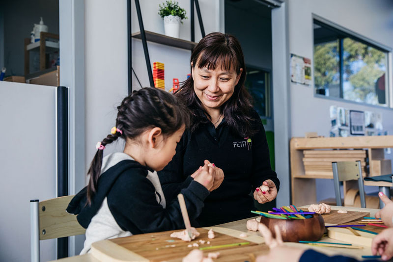 Children use loose parts like craft sticks to make child-made gift ideas.