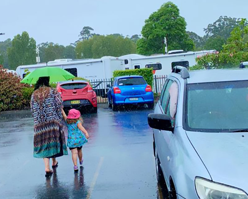 Travelling with children in a car may require umbrellas for rainy adventures.