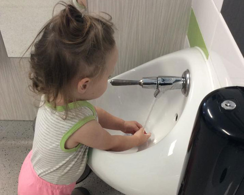 Child learns to wash hands to hand washing songs.