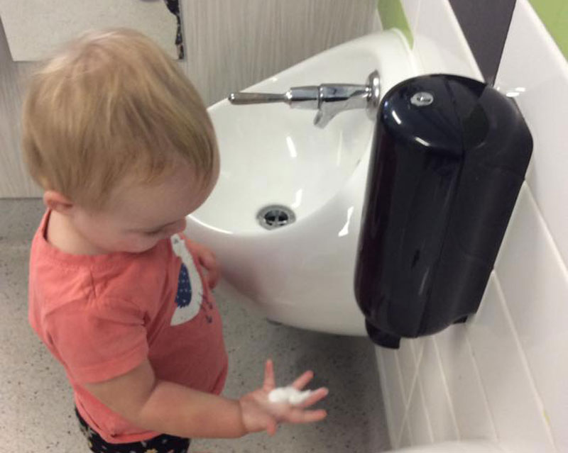 Child observes the sensation of foam while learning how to wash your hands.