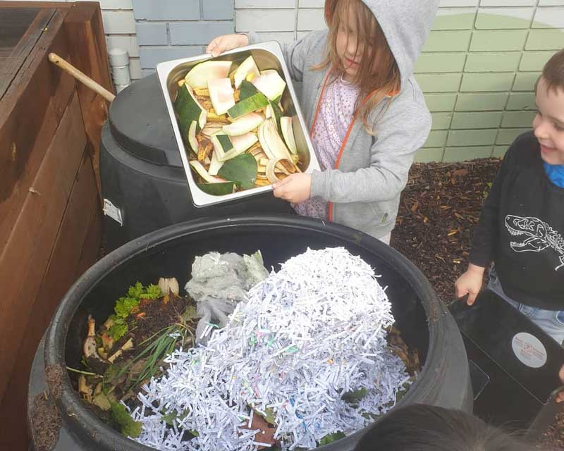 Children engage in composting, one of several Earth Day activities for toddlers.