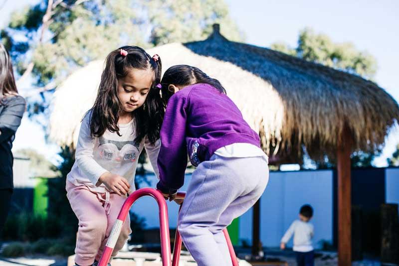 Teaching children kindness: Two children help each other navigate a climbing activity.