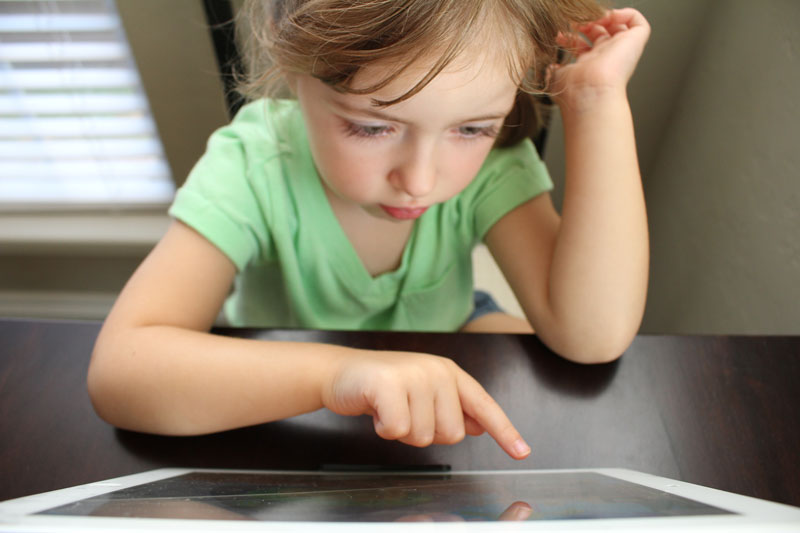 Child sits with tablet learning with some of the best educational apps for preschoolers.