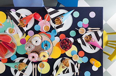 Die Donut-Torte wird auf der Tischdecke mit Punkten platziert (Foto: Anne Deppe)