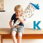 Schultuete von tinyday Kind hält eien Schultuete im Arm und sitzt auf einem Holztisch Buchstaben personalisierbare Zuckertuete Stempel Zelt Einschulung der erste Schultag Schulanfänger