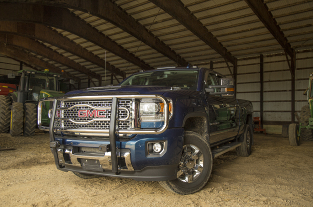 GMC Sierra 3500HD with LUVERNE chrome grille guard in the barn by the tractor