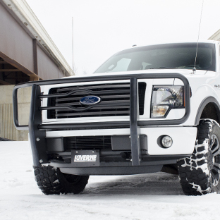 White Ford F150 with a black grille guard from LUVERNE in the snow