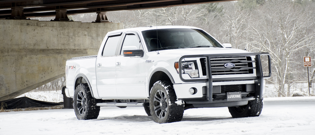 White Ford F150 in the snow with a black LUVERNE grille guard