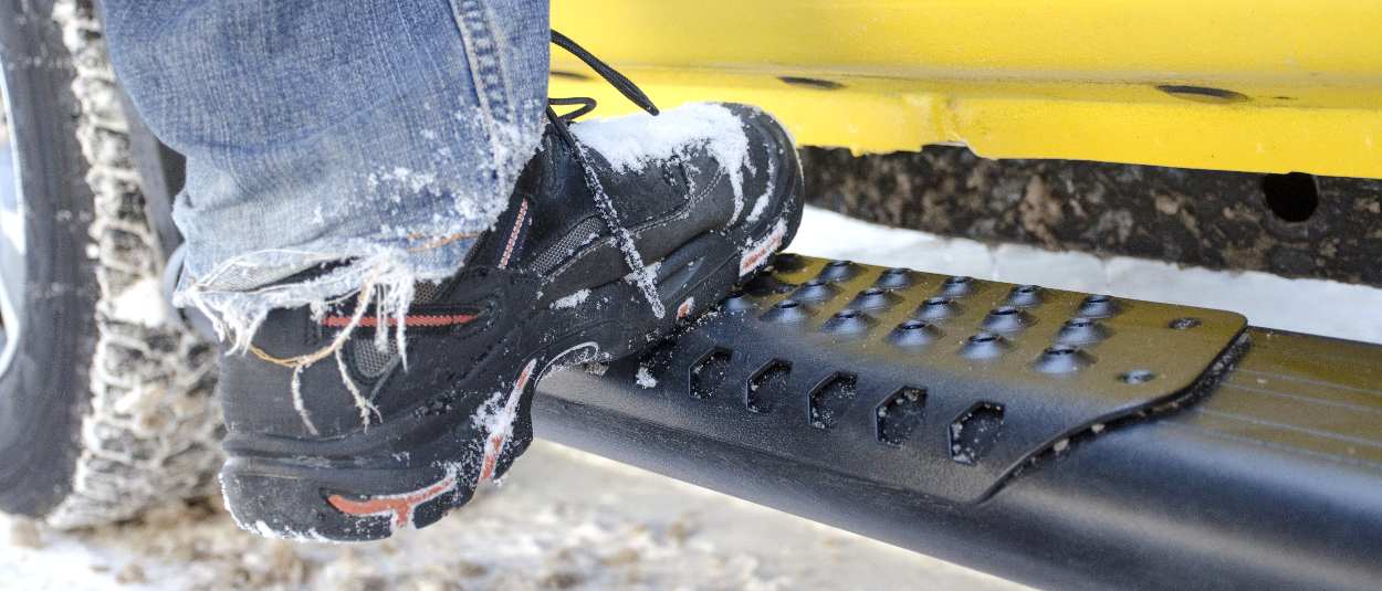 O-Mega II™ aluminum side steps with work boots in the snow