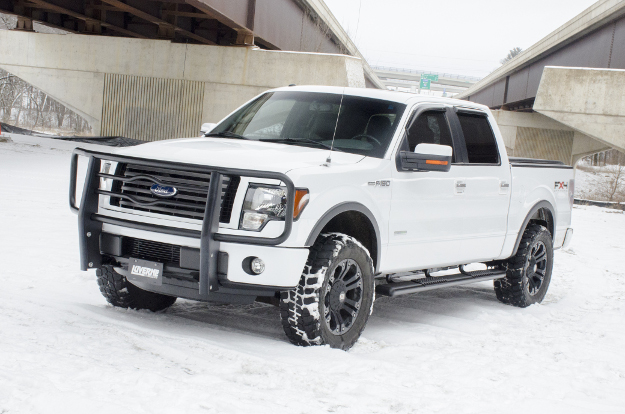 White Ford F150 in the snow with O-Mega II™ side steps and brush guard