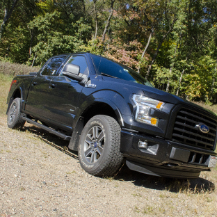 Black Ford F150 with SlimGrip™ running boards in the forest