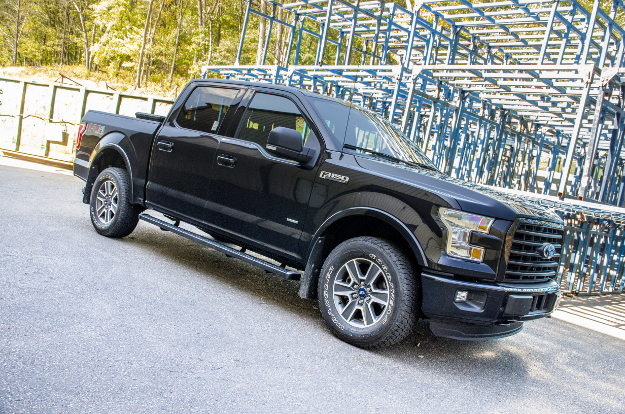 Black Ford F150 with SlimGrip™ running boards by power station