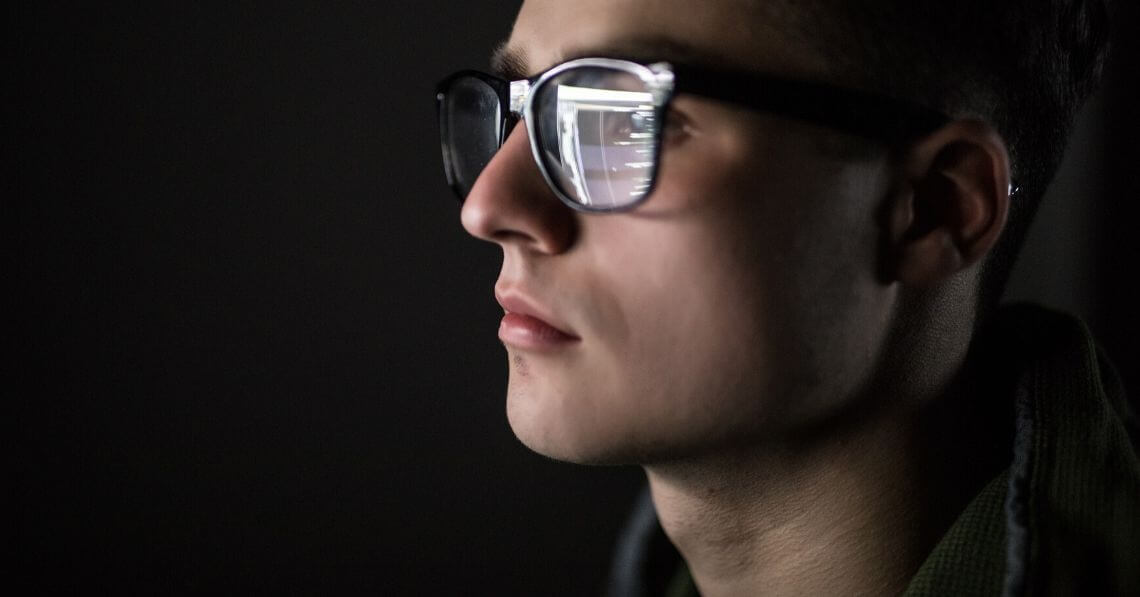 A man wearing blue light blocking glasses