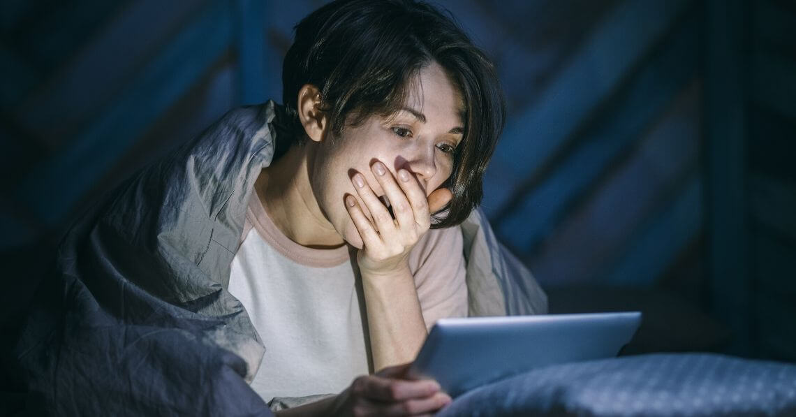 A person yawning while using their tablet late at night