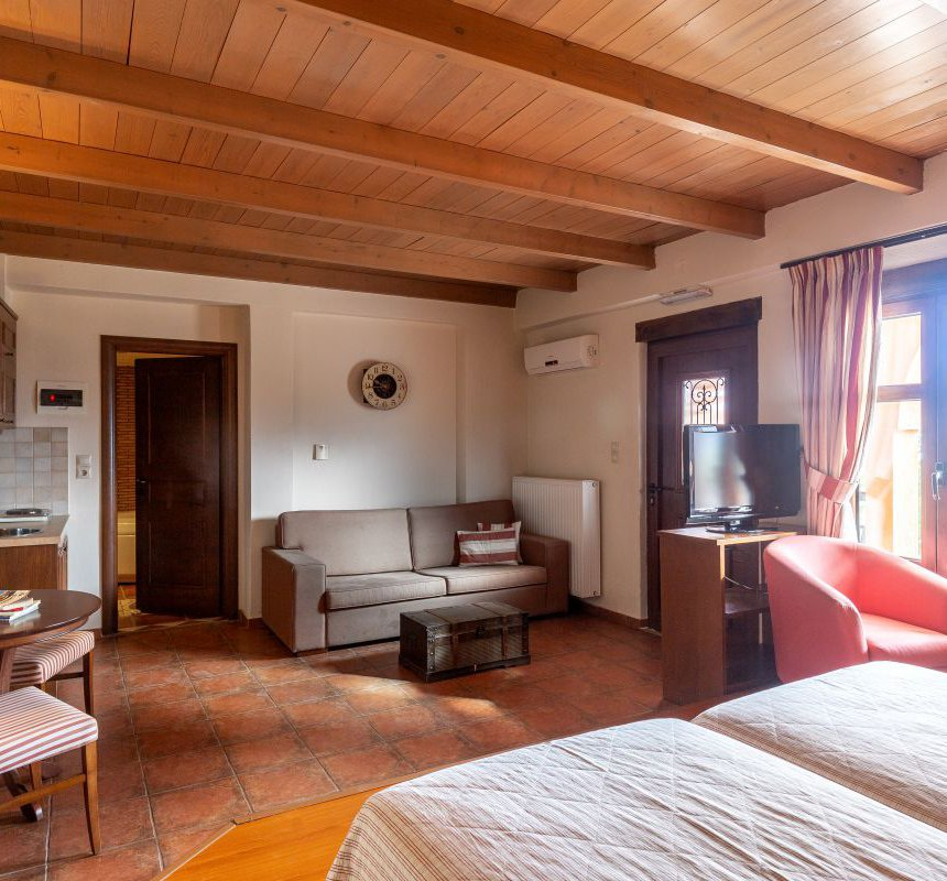 The interior of the residence with the two single beds, the TV, the table with the chairs, the kitchen with the cupboards, the sofa with the coffe table, the stone walls in one side and the white walls in the other, as long as the wooden ceiling