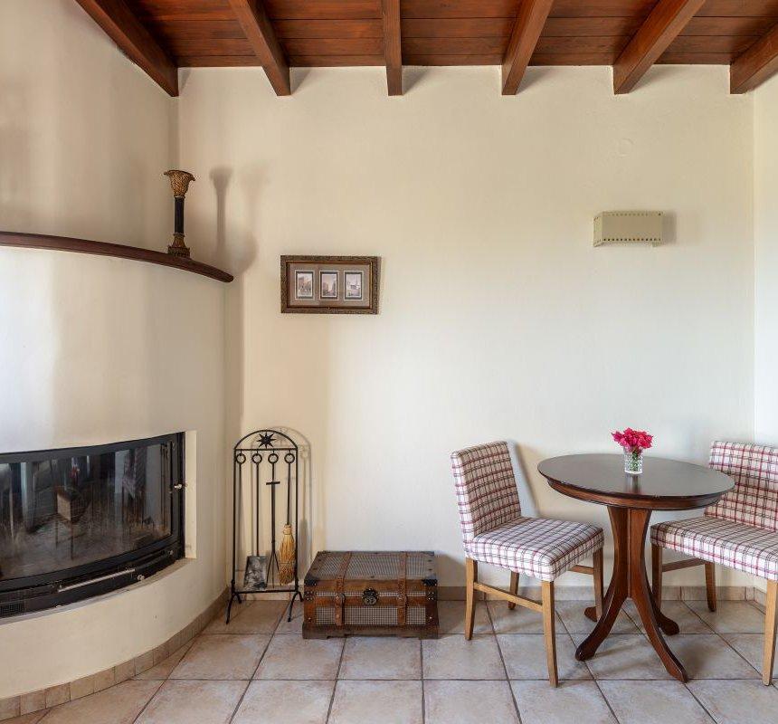 Το εσωτερικό της κατοικίας με το μοντέρνο τζάκι, το τραπέζι και τις καρέκλες, τους λευκούς τοίχους και την ξύλινη οροφή