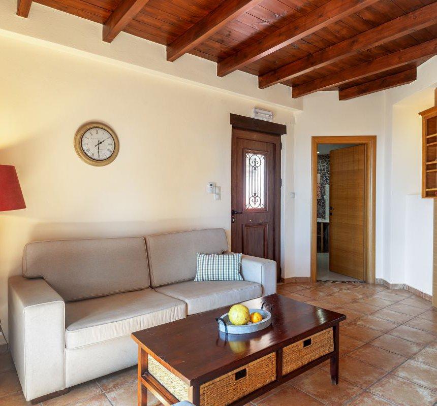 Το εσωτερικό της μεζονέτας με το μοντέρνο φωτιστικό, ο καναπές με το ρολόι τοίχου πάνω του, το τραπεζάκι του καφέ με τα φρούτα από πάνω του, τα ράφια από την άλλη πλευρά και η ξύλινη οροφή από πάνω
