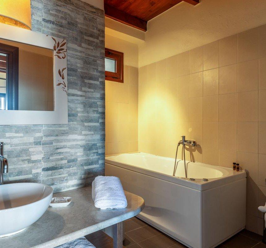 Το λουτρό της κατοικίας με τον νιπτήρα και τον καθρέφτη, μια πετσέτα, την ευρύχωρό jacuzzi με χαμηλό φωτισμό και την ξύλινη οροφή