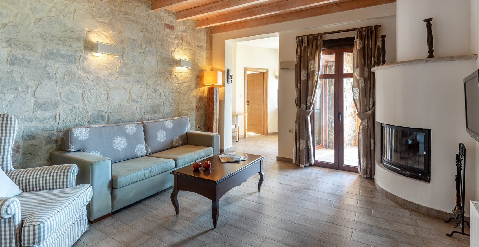 The interior of the maisonette with the stone walls, modern lights, balcony doors, the sofa, coffee table and fireplace