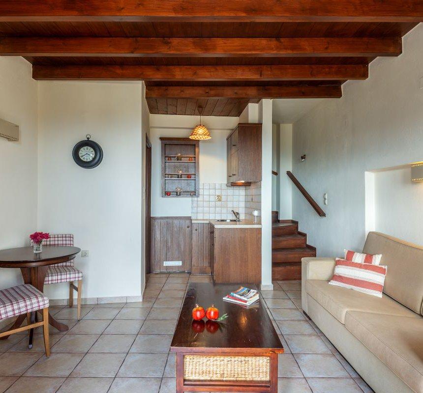 Το εσωτερικό της κατοικίας με την κουζίνα και τα ντουλάπια, το στρογγυλό τραπέζι και τις καρέκλες, τον καναπέ, το τραπεζάκι του καφέ, τους λευκούς τοίχους και την ξύλινη οροφή και τις ξύλινες σκάλες στον πάνω όροφο