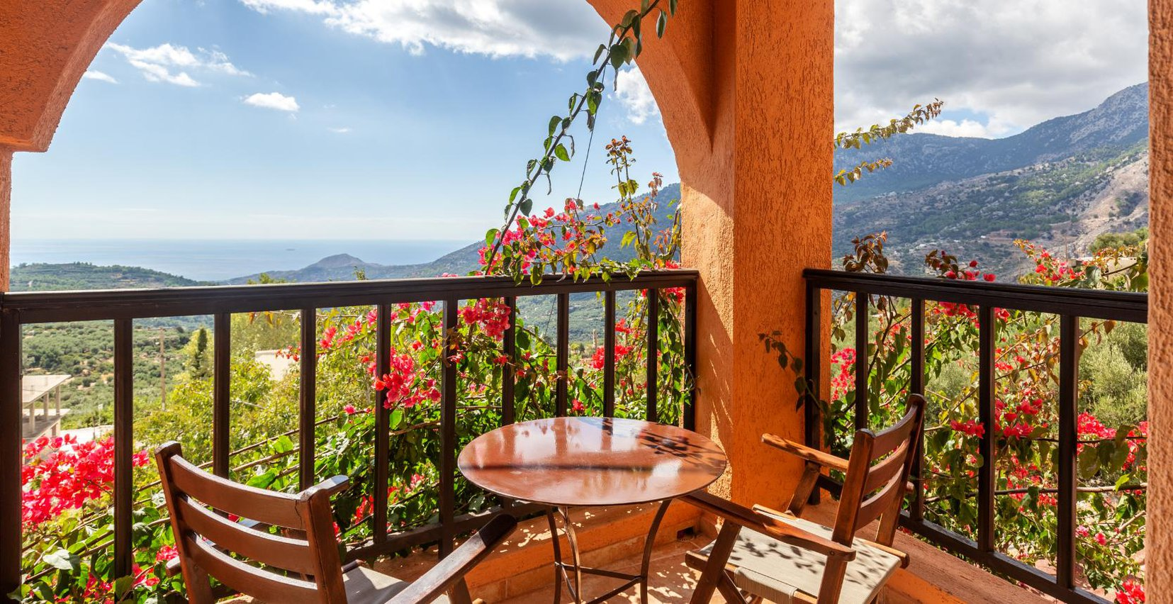 The balcony of the Mint maisonette of Mala Villa with a table, chairs, the plants, and the view of the mountains in the background