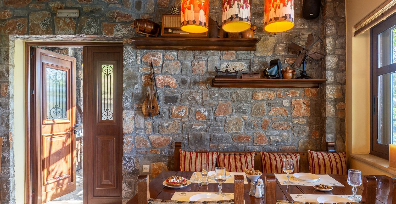 The interior of the restaurant, with the stone walls, decorations, dinner table with plates and food and the sofa