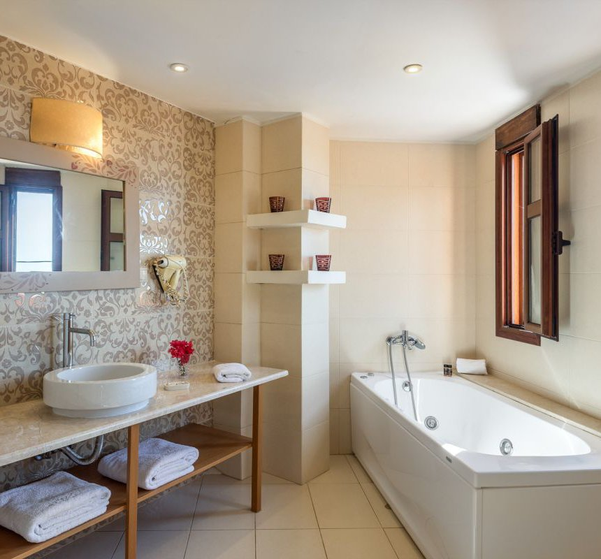 The bathroom of the maisonette with the sink, the mirror, the modern decoration, the towels, the jacuzzi next to the sink and the windows with the beautiful view