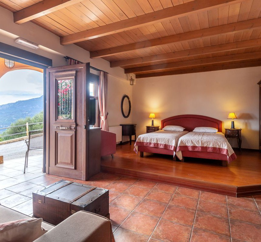The interior of the residence with the two single beds, the bedside tables, the closet, the coffee table, the sofa, the window and the door with the porch and the view on the beautiful mountains