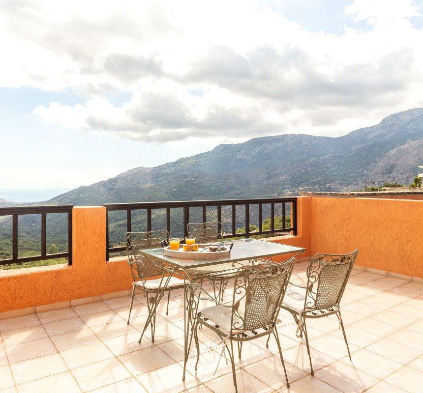 Delicious breakfast on the balcony of the maisonette, with the view of the Malles mountains and the sea in the background