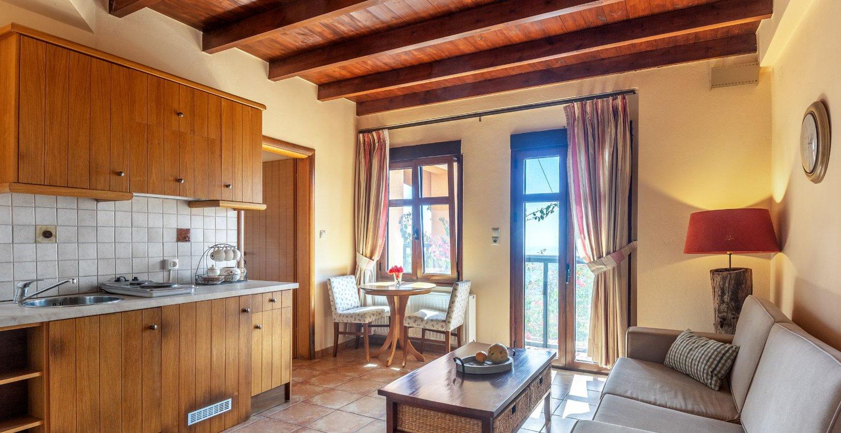 Η κουζίνα και το σαλόνι της μεζονέτας με το νεροχύτη, τα συρτάρια, τα μάτια της κουζίνας, το τραπέζι με τις καρέκλες, ο καναπές με το τραπεζάκι του καφέ και η μπαλκονόπορτα με την όμορφη θέα