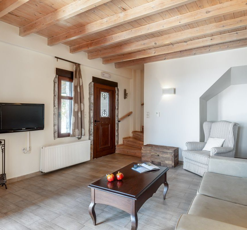 The lower floor of the maisonette with the wooden stairs, the door and window, the TV, the fireplace, the sofa with the stone wall behind it, the coffee table and the armchair