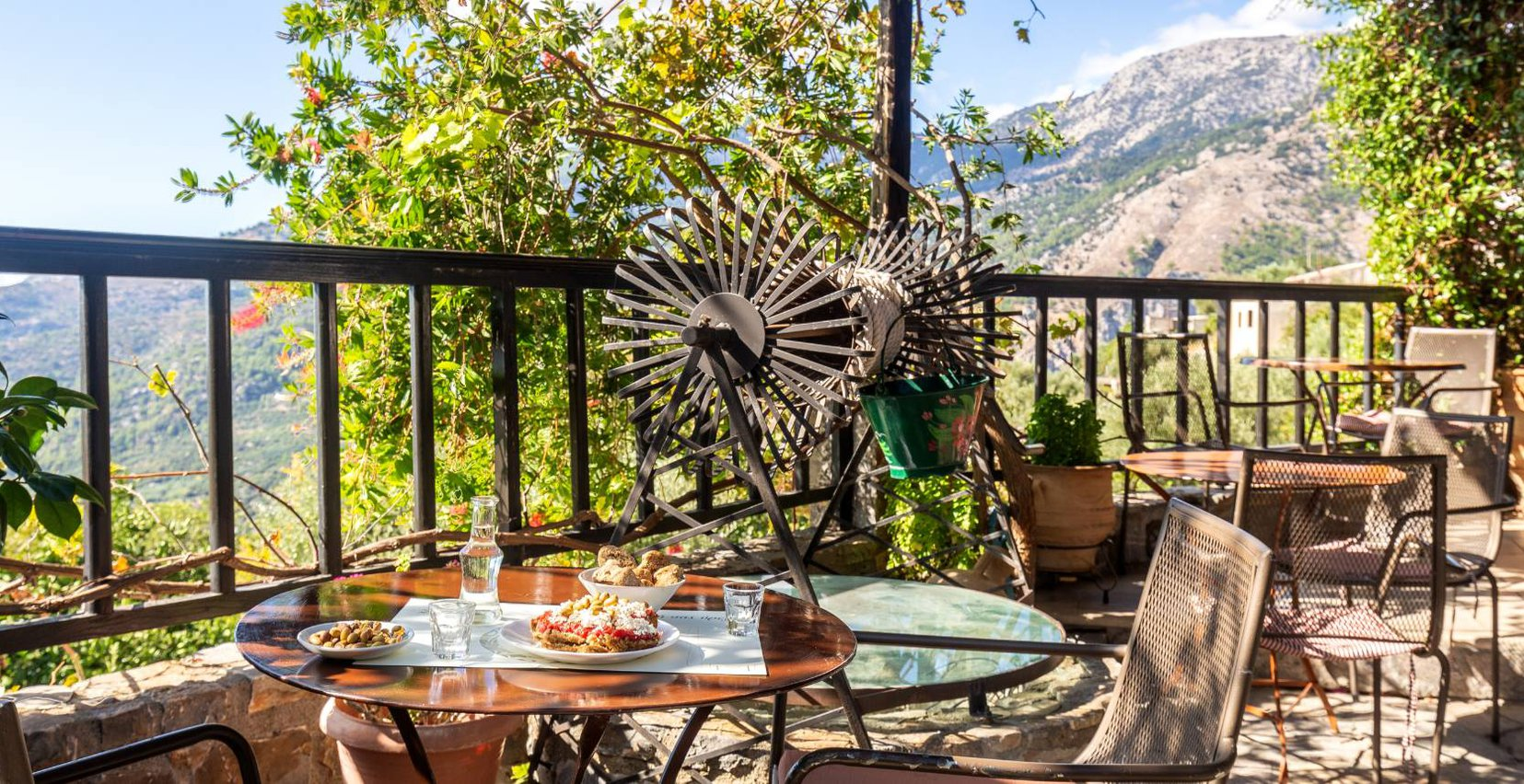 The outdoors restaurant of Mala Villa with the tables with delicious food like cretan ntakos, olives, Cretan raki, bread, the old renovated well in the side of the area, and the view of the beautiful mountains