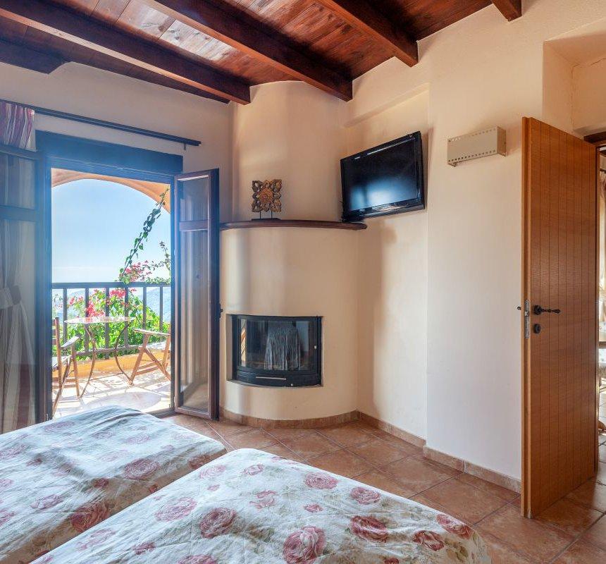 Το εσωτερικό της μεζονέτας με τα δύο μονά κρεβάτια, το τζάκι, την τηλεόραση, τον καναπέ στο σαλόνι της μεζονέτας και την μπαλκονόπορτα με την όμορφη θέα