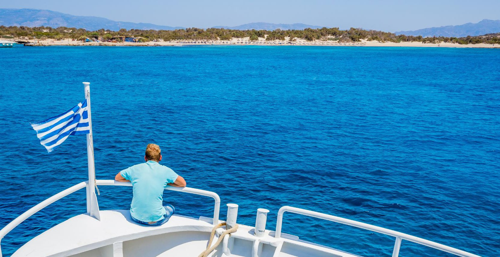 Man watching the sea from the stern of a boat in the sea