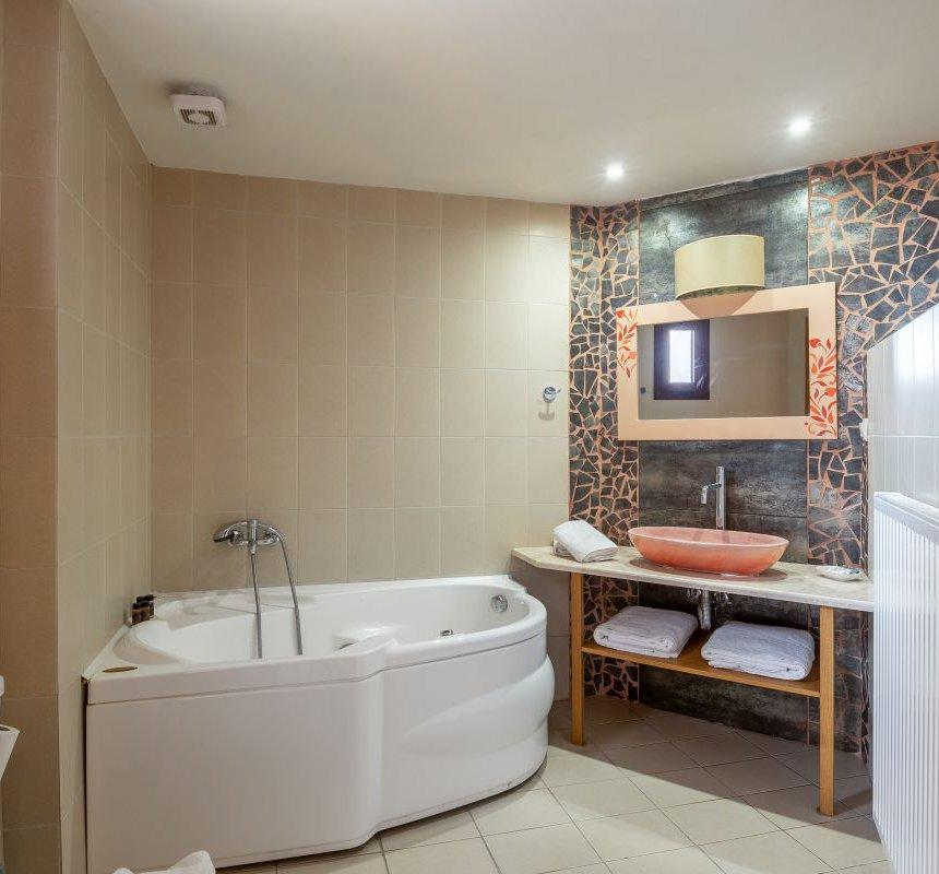 Το λουτρό της μεζονέτας με τον νιπτήρα, τον καθρέφτη και τις πετσέτες, τους μοντέρνους τοίχους και το τζακούζι δίπλα στο νεροχύτη