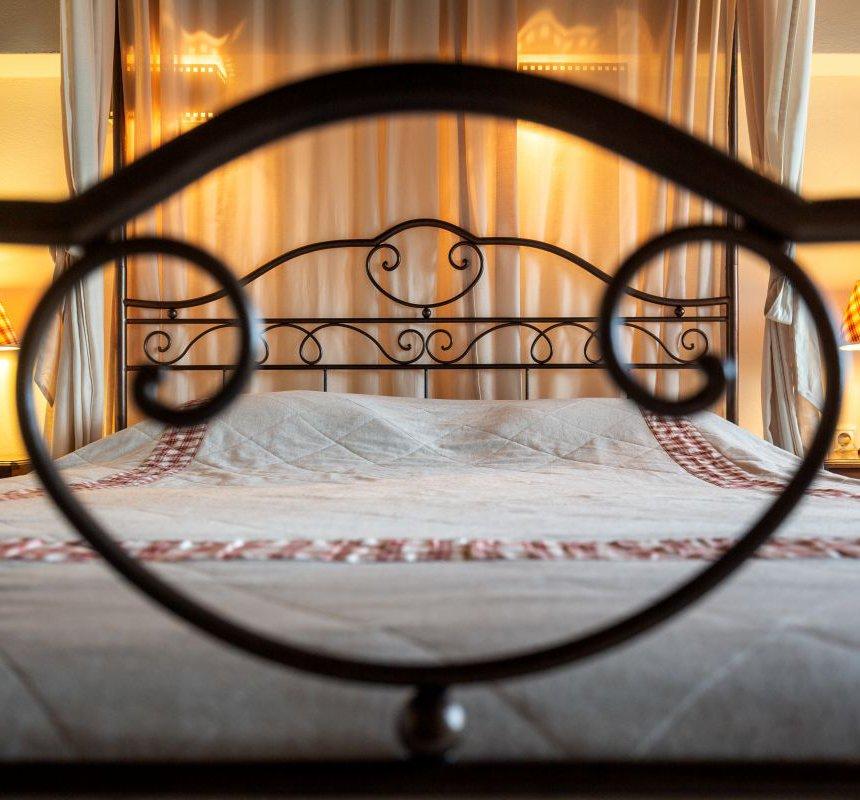 Το ευρύχωρο κρεβάτι της κατοικίας με τις κουρτίνες γύρω του, και τα κομοδίνα με τα φώτα από πάνω τους
