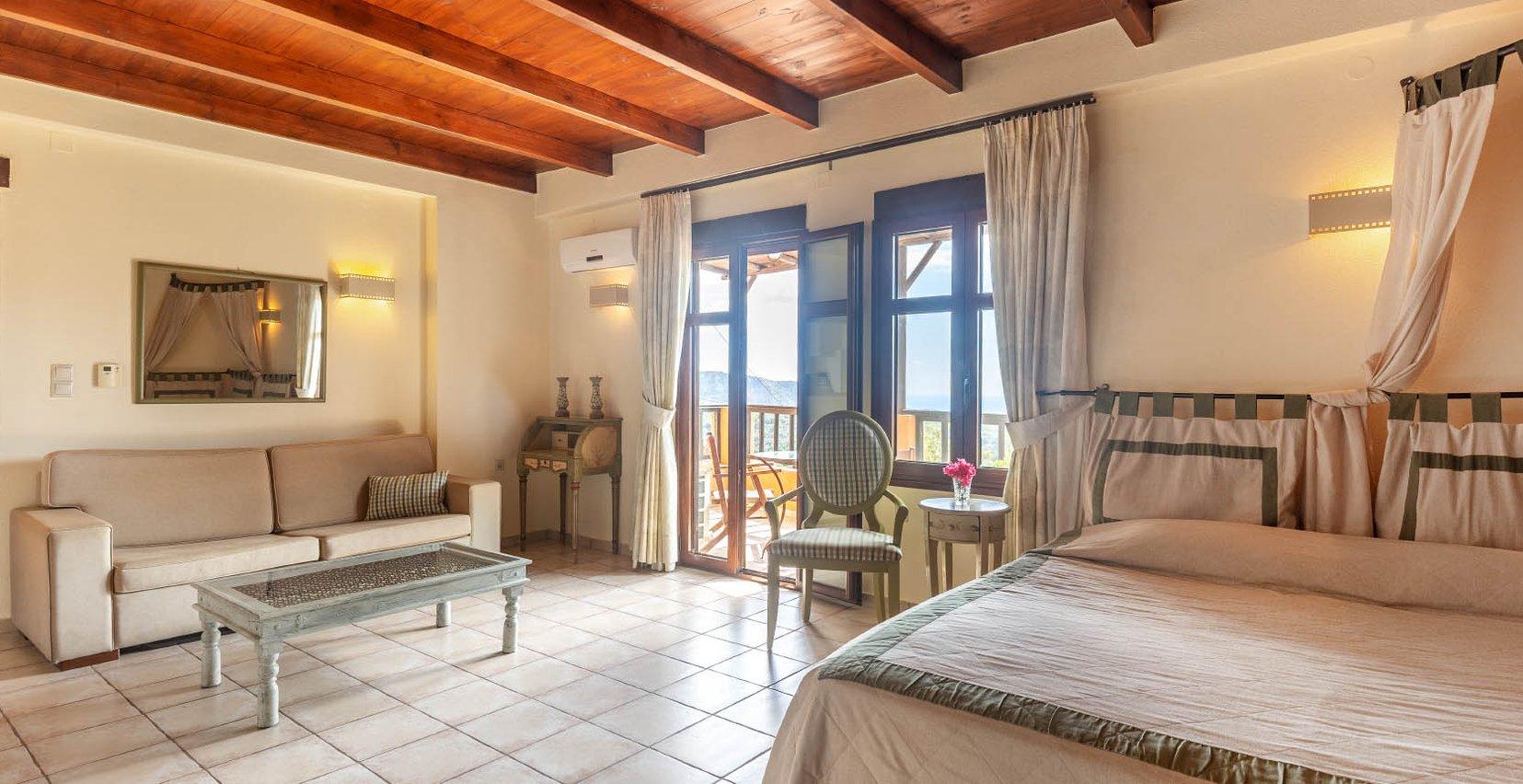Το εσωτερικό απο την κατοικία Μαντζουράνα του Mala Villa με τον καναπέ, το τραπεζάκι του καφέ, τα μοντέρνα φώτα, τις μπαλκονόπορτες και το τεράστιο κρεβάτι