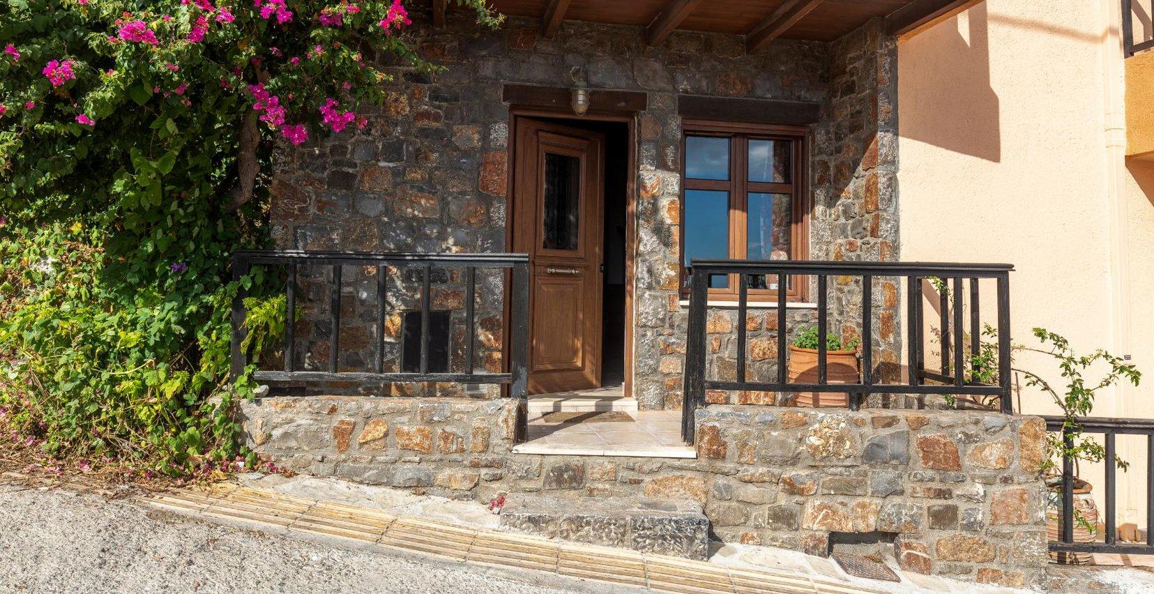 Η είσοδος της κατοικίας με τους πέτρινους τοίχους, και τα σκαλοπατάκια που οδηγούν στην βεράντα με την πρασινάδα από γύρω