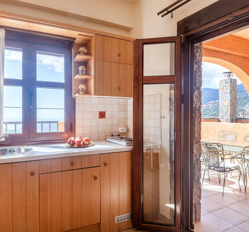 The kitchen of the maisonette, with the window overlooking the mountains, and the spacious balcony next to it, with the beautiful view