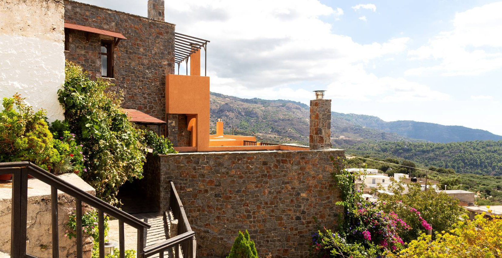 The exterior of the residences of Mala Villa with the greenery and the mountains in the background
