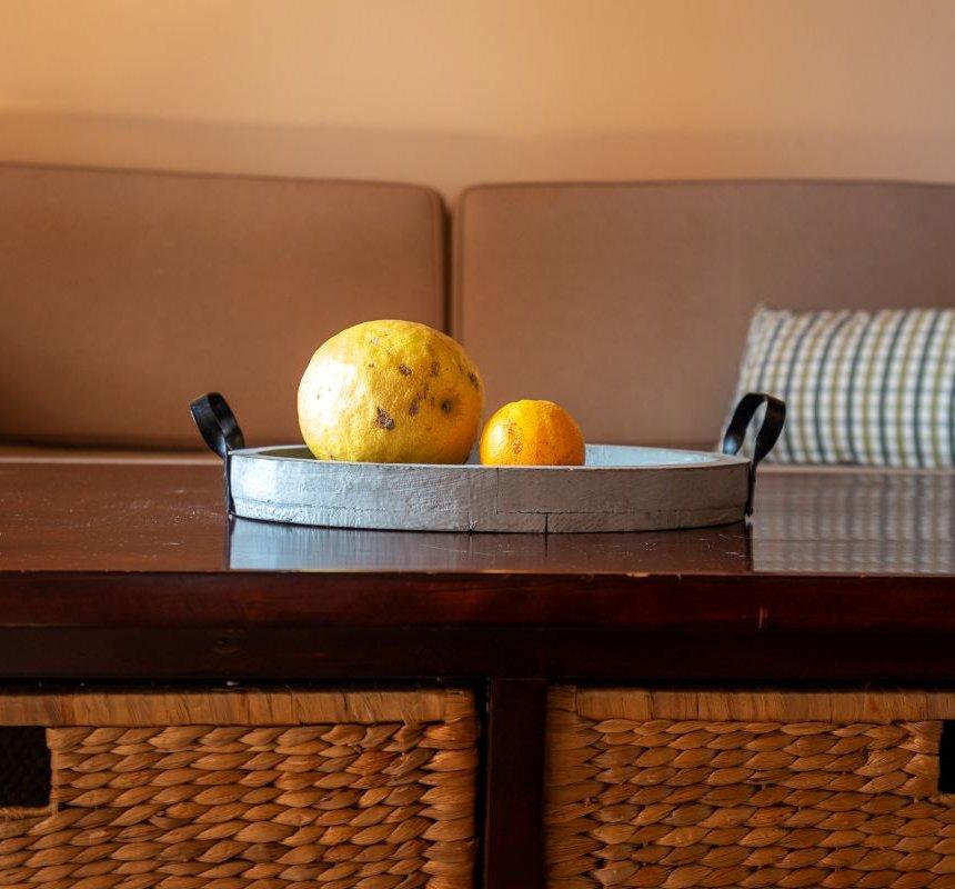 Φρούτα πάνω σε ένα τραπεζάκι σαλονιού με τον καναπέ στο παρασκήνιο