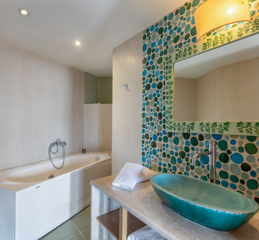 The bathroom of the residence with the sink and mirror, a towel, the spacious jacuzzi and modern lights