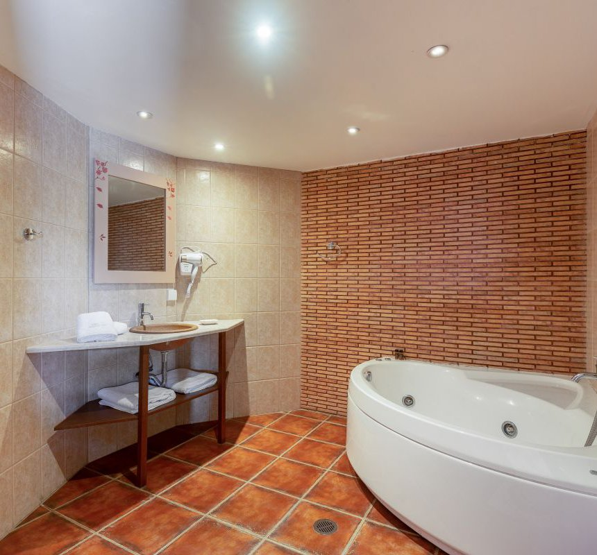 The bathroom of the residence with the sink, the mirror and the towels and the spacious jacuzzi