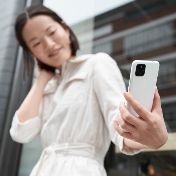 スマートフォンを見つめている白色のシャツを着た女性。