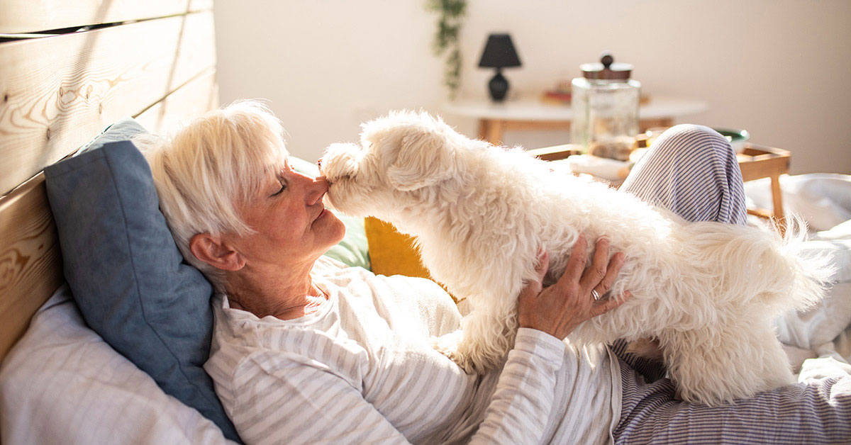 Senior woman enjoys time with her dog in her pet friendly senior living apartment.