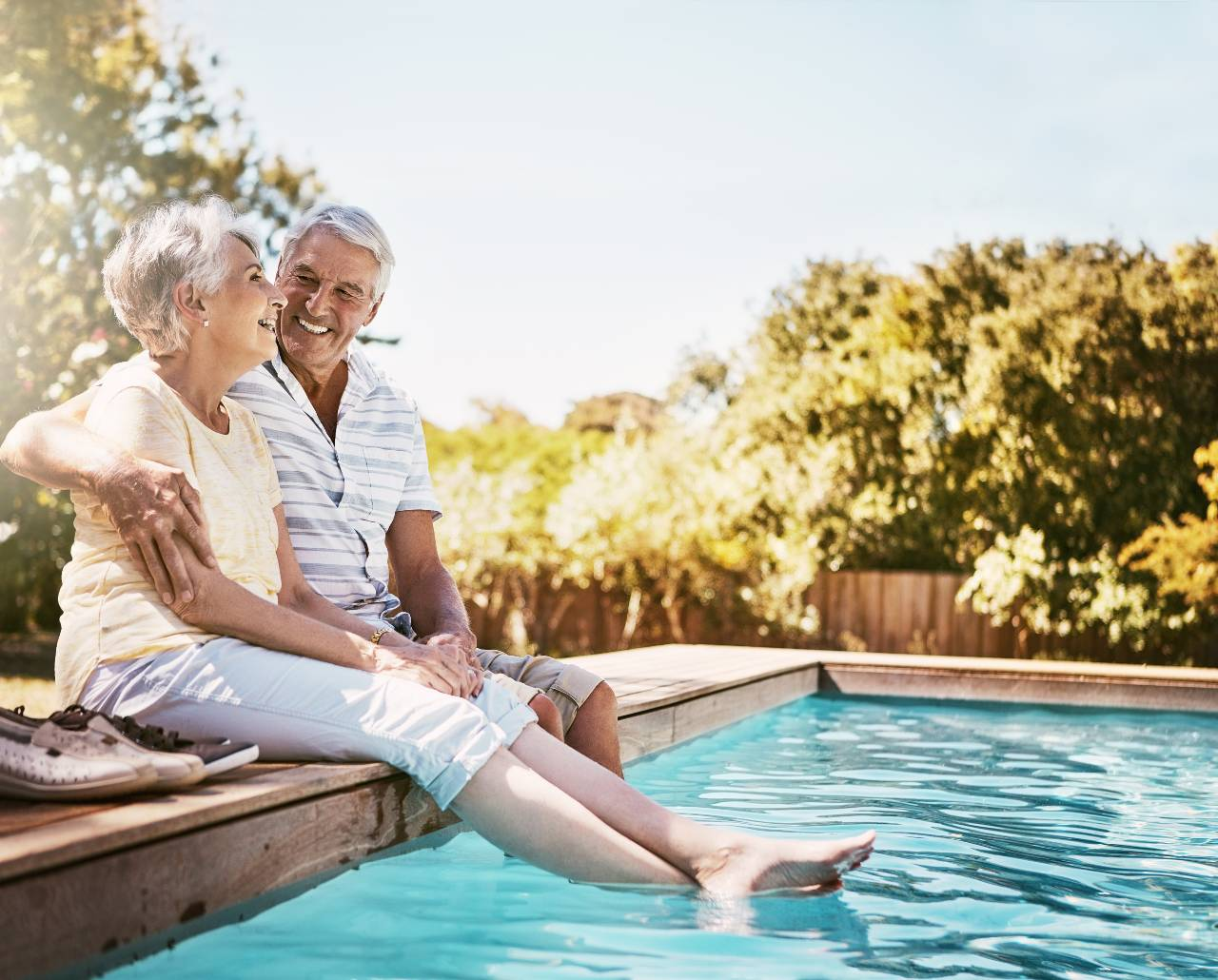 Senior couple with their feet in the pool
