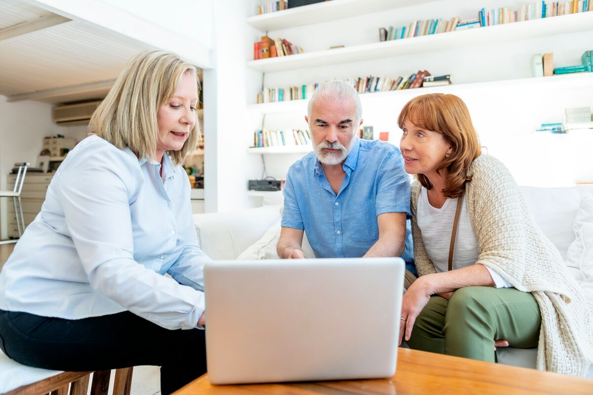 Senior couple talking with someone and looking at a laptop